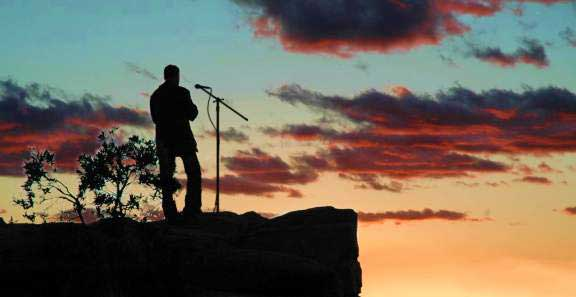Jim Meskimen at sunset on a cliff with a microphone creating voices